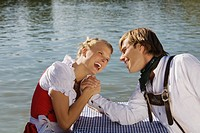 Young couple in traditional Bavarian outfit, arm-wrestling in Beer garden (thumbnail)