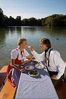 Young couple in traditional Bavarian outfit, eating meal in beer garden, Munich