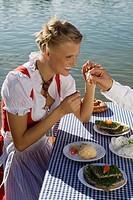 Young woman in traditional Bavarian outfit, eating meal in beer garden, Munich