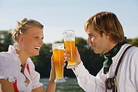 Young couple in traditional Bavarian outfit, drinking beer in beer garden Munich