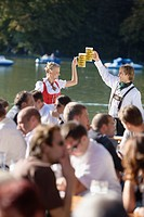 Young couple in traditional Bavarian outfit, toasting with beer glasses in crowd