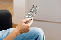 Woman holding TV remote control