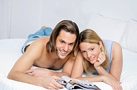 Young couple in bed, watching television