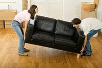Young couple moving sofa