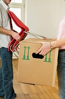 Young couple carrying furniture
