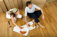 Couple eating pizza in new home