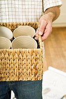 Man carrying basket of crockery