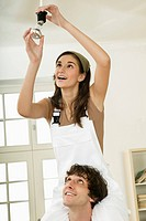 Young couple changing light bulb