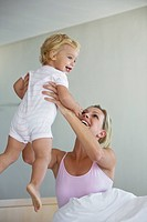 Young mother playing with baby 12_24 months in bedroom