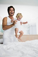 Young father playing with baby 12_24 months in bed, holding up baby, laughing