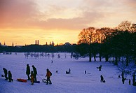 Group of people riding sledges in English Garden, Munich, Bavaria, Germany
