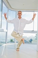 Senior man standing on one leg, doing Yoga exercise, indoors