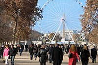 Crowd in Jardin des Tuileries garden, with Ferris wheel in background ,Paris