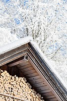 Snow covered wooden hut with stack of wood, Grainau, Bavaria, Germany