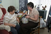 Community nurse with a 64_year_old patient in her home. The nurse right is going through the patient´s different prescription medications in order to ...