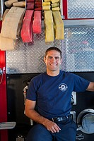 Hispanic fireman leaning against fire engine