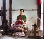 Asian woman working on loom