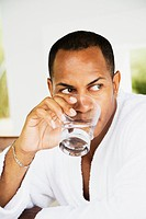 Mixed race man in bathrobe drinking water