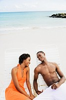 African couple sitting in lounge chairs on beach