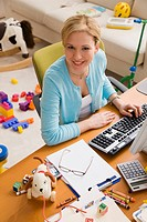Hispanic woman working at desk surrounded by toys