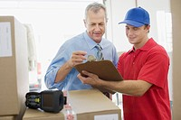 Businessman talking with delivery man in warehouse (thumbnail)