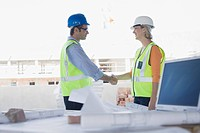 Co_workers shaking hands on construction site