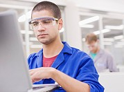 Worker in coveralls and safety goggles using laptop