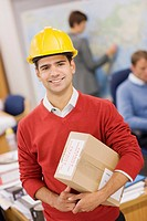 Businessman in hard_hat standing in office holding box