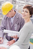 Businesswoman holding blueprints in office with construction foreman