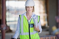 Businesswoman in hard_hat and safety vest holding blueprints