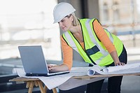 Businesswoman in hard_hat reviewing blueprints and using laptop