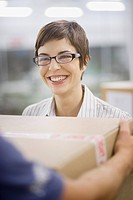 Businesswoman taking box from delivery man