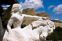 Model of Crazy Horse sculpture with the uncompleted sculpture on Thunder Mountain in background, Crazy Horse Memorial, Black Hills, South Dakota USA