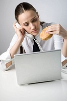 Business Woman on Phone Eating Sandwich and Working