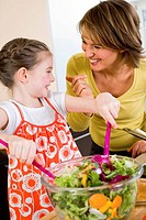 young girl and mother making salad