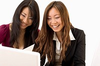 portrait of two asian woman in front of computer