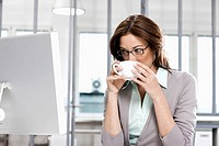 portrait of businesswoman sitting in front of computer drinking coffee