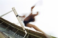 Runner jumping over hurdle, blurred