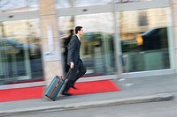 Businessman running down sidewalk, pulling suitcase behind him
