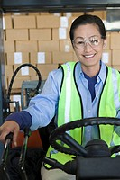 Cheerful Asian woman working in distribution warehouse