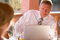 Businessman with laptop on restaurant balcony