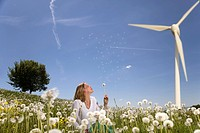 woman blowing dandelion at wind turbine