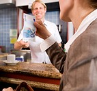 businesswoman paying barkeeper in bar