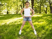 Mixed race girl with hands on hips in grass