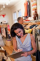 Hispanic business owner taking telephone order in clothing store
