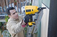 Hispanic man drilling siding on house