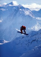 Snowboarder jumping with mountain view