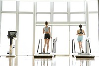 Two young women on walker as they exercise in a well equipped gym