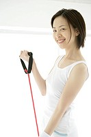 A young woman smiles as she uses the stretching rope for an exercise (thumbnail)