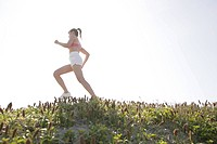 Side view of a woman jogging during bright sunlight